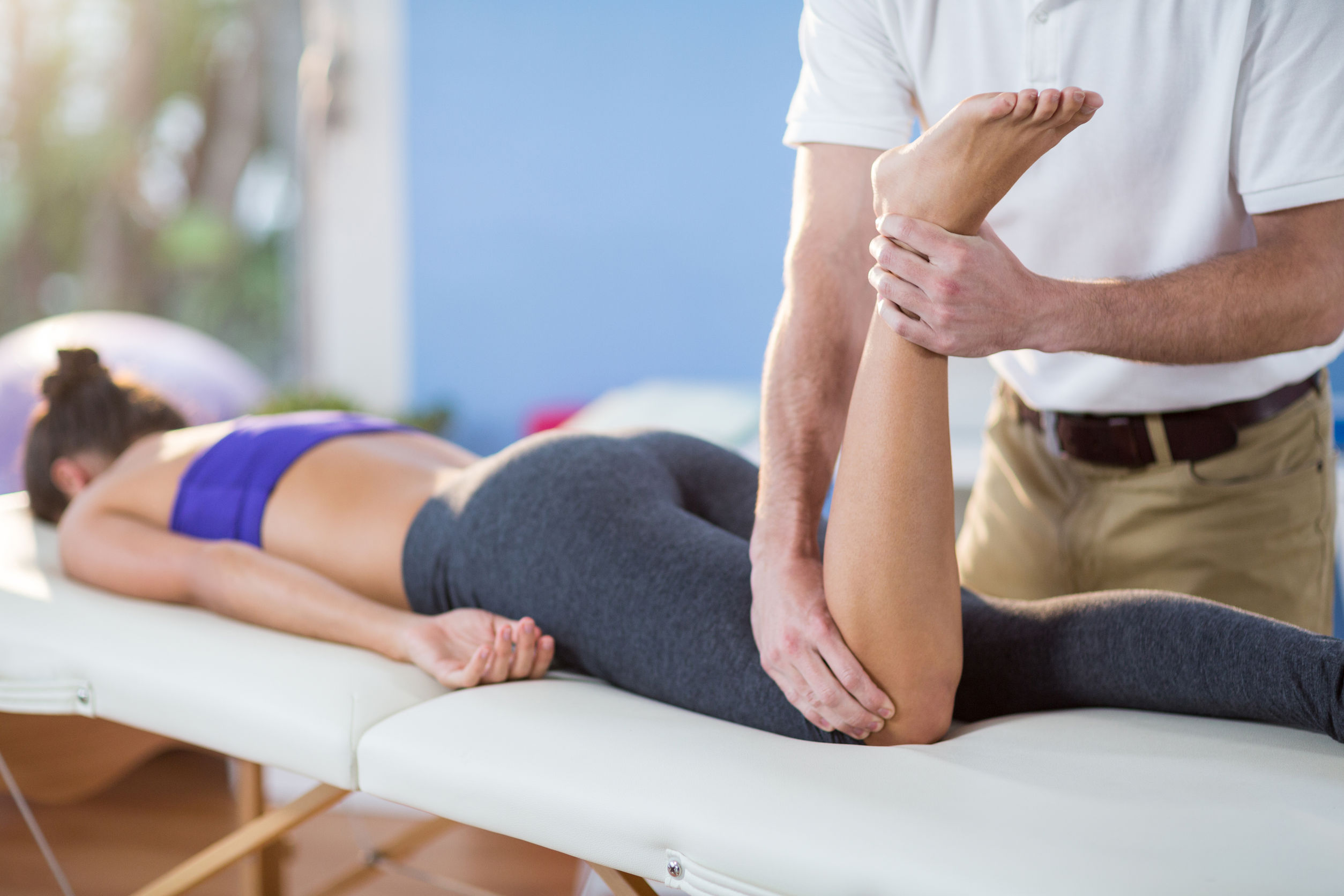 62064117 - male physiotherapist giving knee massage to female patient in clinic